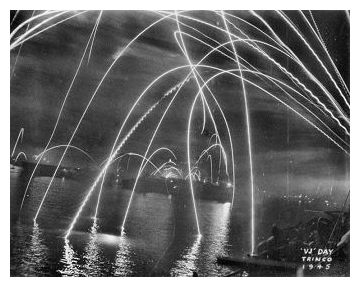 HMS EMPRESS and other ships of the East Indies Fleet in Trincomalee harbour alight with fireworks to celebrate Victory over Japan, V-J night. August 15th 1945.  Photo:  Courtesy John Browne.