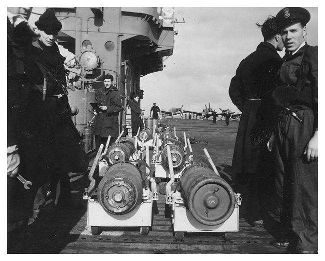 Armourers wait to load bombs onto the aircraft in preparation for an upcoming strike. Photo: Jack Price via Carl Berrington