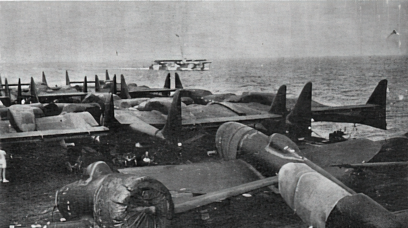 PUNCHER's deck cargo included a number of the twin tail boomed P-61 'Black Widows' of the 427th Night Fighter Squadron USAAF; a couple of P-47 Thunderbolts, can be seen towards the front of the flight deck .  The USS SHAMROCK BAY is in the background.